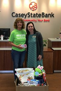 two woman standing at casey state bank desk in front of a box of dog goods